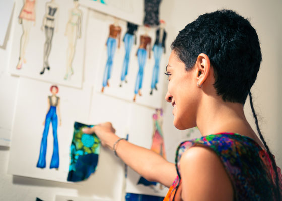 Hispanic woman at work as fashion designer looking at sketches
